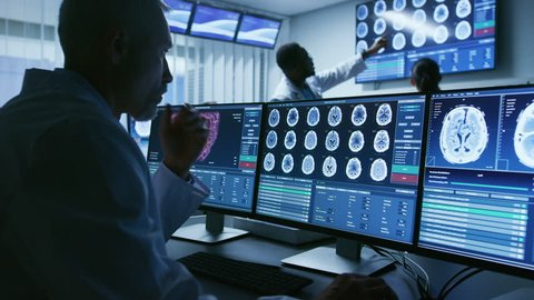 Over the Shoulder Shot of Senior Medical Scientist Working with CT Brain Scan Images on a Personal Computer in Laboratory.  Shot on RED EPIC-W 8K Helium Cinema Camera.