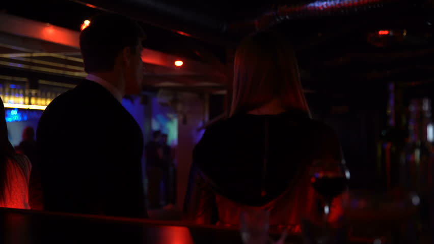 Couple dancing and talking at bar counter, acquaintance in nightclub, back view | Shutterstock HD Video #1013088983