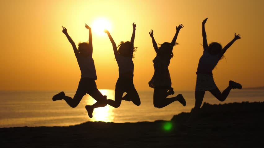 Jumping woman silhouette at sea sunset. Four young women jumping in slow motion on sunset sky. Happy women enjoying evening rest. Summertime lifestyle