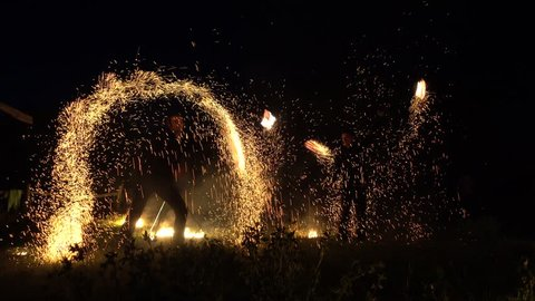 Ivanivka village, Ukraine - 9th of June 2018: Fire show by Nikolaev troop - 4K Artists spinning Indian lights at the outdoor fire show