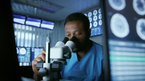 Medical Research Scientist Looking under the Microscope in the Laboratory. Neurologist Solving Puzzles of the Mind and Brain. In the Laboratory with Multiple Screens Showing MRI / CT Brain Scan Images