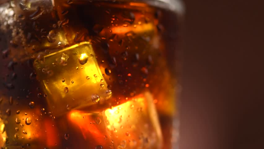 Cola with ice cubes rotated. Glass of Cola drink with Ice and bubbles and water drops on glass. Soda closeup. Food background. Rotation 360 degrees 4K video footage. Ultra high definition 3840X2160