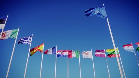 Flags of European Union and european countries against the blue sky. Smooth slowmotion from a 120 fps original shoot
