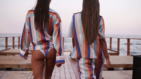 Close up of a two gorgeous tanned models walk by wooden pier. Brunette longhaired fit girls in similar colored summer clothes. Backside view