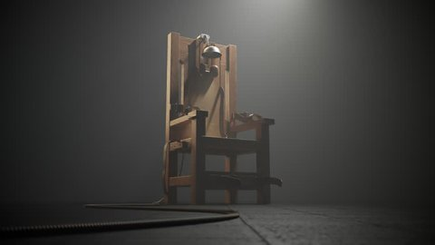 03497 Electric chair in the spotlight. Camera track in.