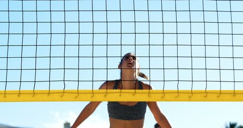 Female volleyball player playing volleyball in the beach 4k