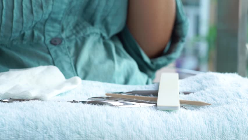 Woman taking nail file for filing nails during home manicure. Manicure tools lying on towel. Home manicure and nail care concept