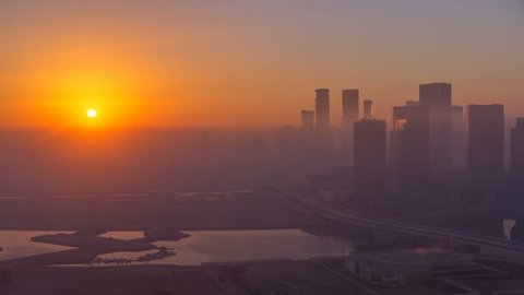 Abu Dhabi city skyline with skyscrapers at sunrise from above timelapse. Aerial view at foggy morning from rooftop