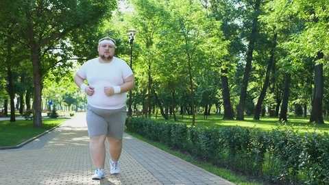 Purposeful fat man running in park, out of breath, persistent motivation
