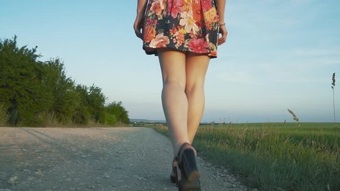 beautiful, attractive European girl with long leggs in short skirt with flowers walks in black heels along the road with gravel,the bottom view, slow motion