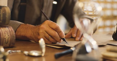 Close up of the old male hands writing a letter with ink on the wooden table in the ancient style.