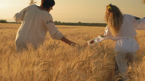 Slow Motion, Two Beautiful Women in National Shirts with Wheat Spikelets in Hands Go along the Wheat Field and Hand Spank Up Growing Spikelets