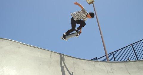 Slow motion skateboarder doing extreme air on vert ramp in skatepark