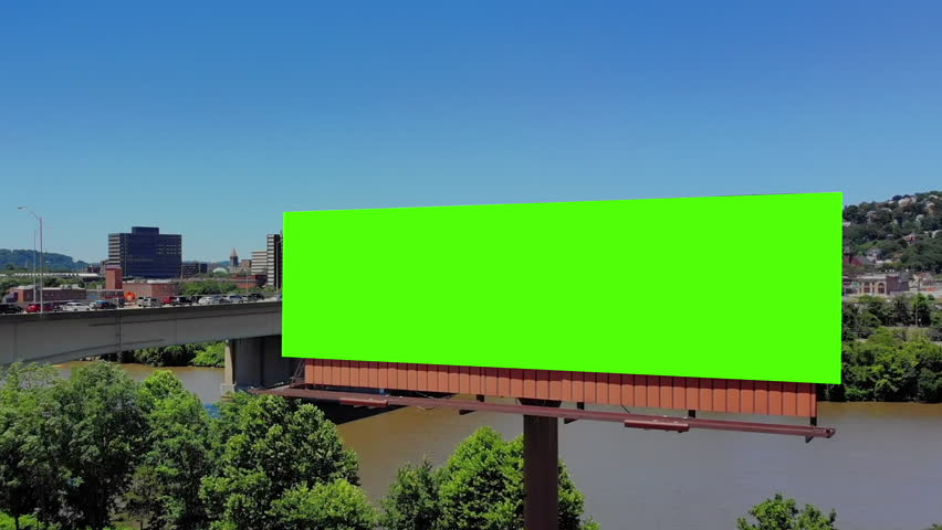 A slow push forward aerial view of a city's billboard. Green screen with optional tracking points for advanced screen replacement. Veterans Bridge over the Allegheny River in the background. Billboard