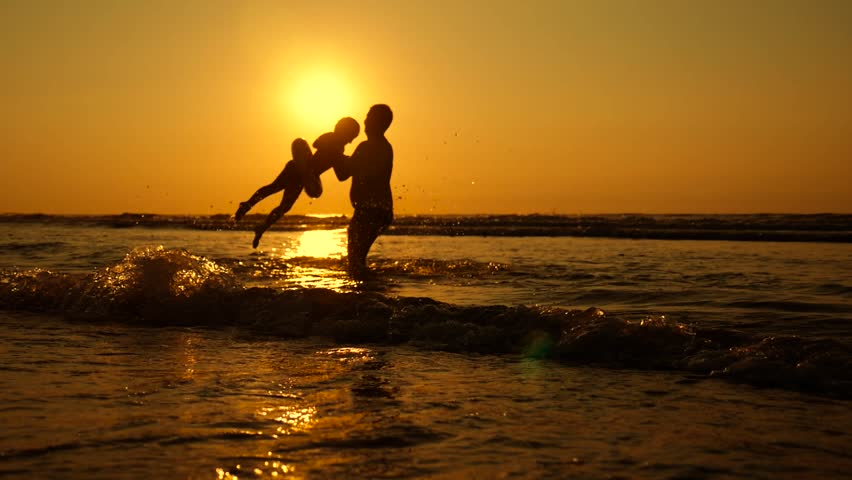 Silhouette of the father and his little daughter are running happily into the sea at sunset. Splashes fly into their faces. Happy family with a child on vacation at the beach. #1013317583