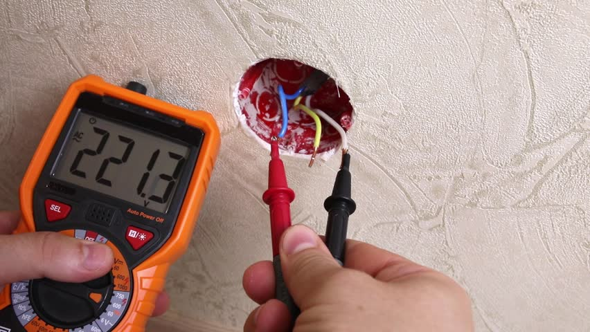 Close-up of man measuring and cheking power supply voltage with digital multimeter