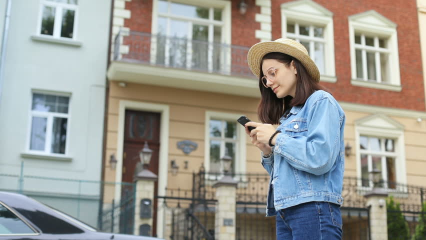 Cute stylish woman in elegant straw hat and jeans jacket using smartphone while standing in front of beautiful modern building social networking online beauty blogger checking website attendance | Shutterstock HD Video #1013337743
