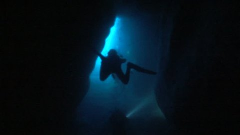 scuba divers coming out of a cave underwater exit