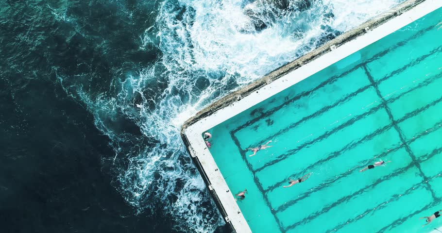 Swimming pool at Bondi Beach, Australia. Aerial shot looking directly down at a section of the pool with swimmers and waves crashing.