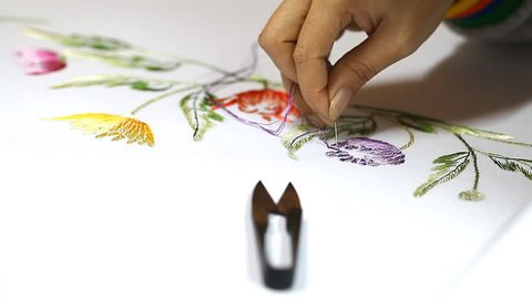 Embroidering a picture with silk thread close-up