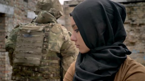 Armed soldier with weapon passing by muslim woman in hijab, woman standing in ruined abandoned building, war concept