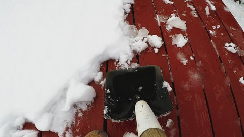 Flagstaff AZ/USA - January 15, 2018: Shovel cam point of view of shoveling snow off a wood deck. Clip provides an unique perspective to a normal winter task or chore.
