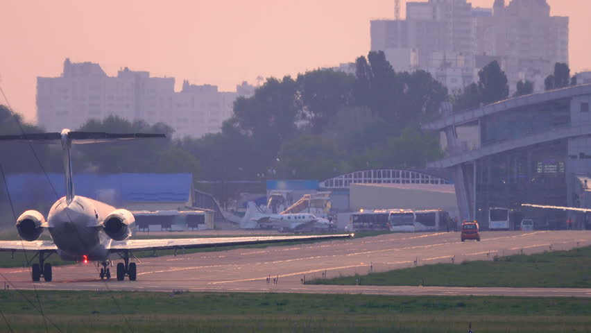 Airplane taxiing on the taxiway to airport terminal after landing at sunset. Back view