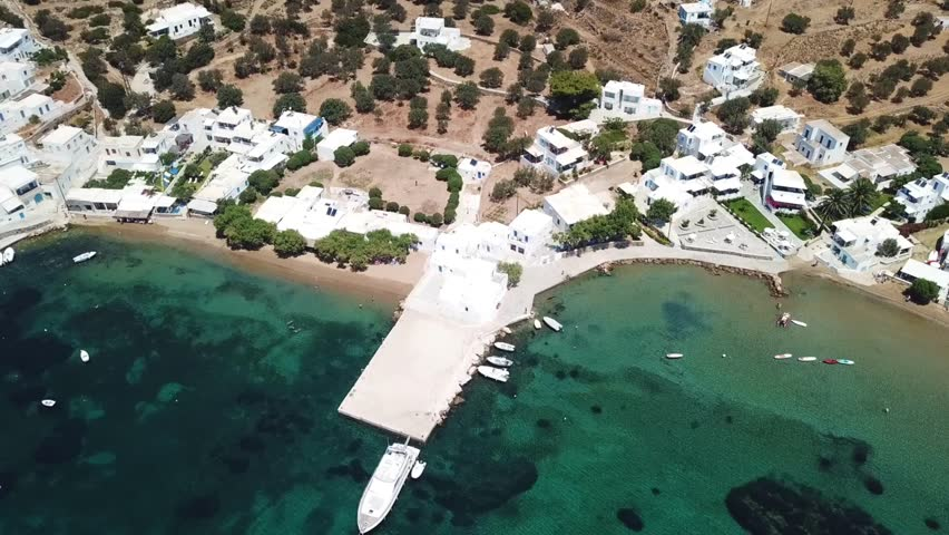 Aerial drone bird's eye view video from famous and picturesque bay and fishing village of Vathi with iconic whitewashed church of Taxiarhis and turquoise clear waters, Sifnos island, Cyclades, Greece | Shutterstock HD Video #1013444513