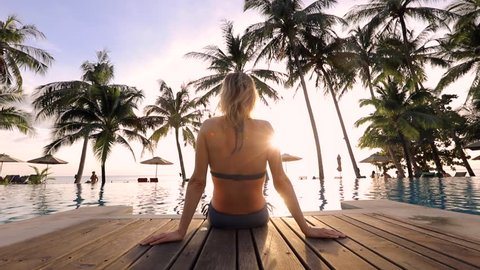 Woman relaxing by the pool in a luxurious beachfront hotel resort spa at sunset enjoying perfect beach holiday vacation, traveling footage