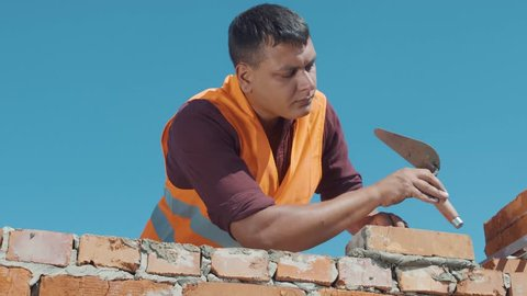 Bricklayer build wall on a blue sky background