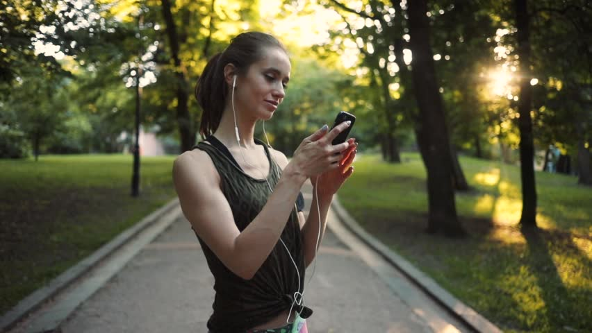 Beautiful woman use smartphone in park slow motion sun outdoor health hand girl tree sport fitness summer nature internet technology female runner exercise phone workout young mobile cellphone closeup