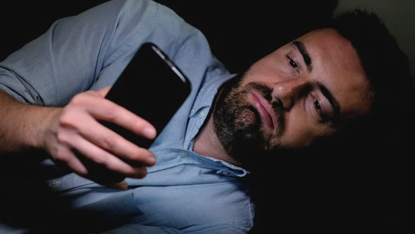 The video is about one tired man using smartphone at night and yawning on the sofa.The shot is fixed on the man. | Shutterstock HD Video #1013486363