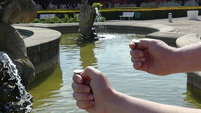 Prague, Czech Republic - May 7, 2018: The hand throws a coin for good luck in the fountain. Hand blotted a coin into the fountain. The tradition of throwing a coin into a fountain.