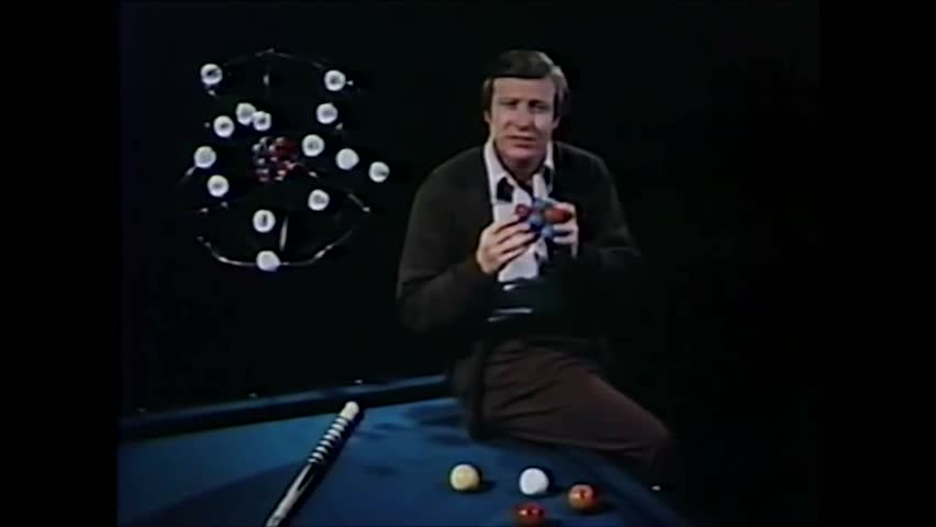 CIRCA 1970s - The formula demonstrating Mass_energy equivalence is shown as a scientist uses billiard balls to explain fusion reactions.