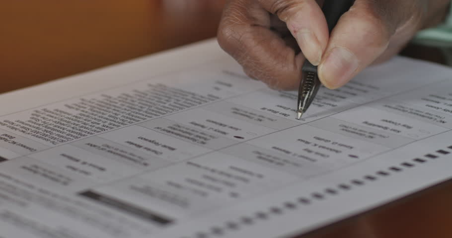 Senior black hand voting on a voter paper ballot in an election