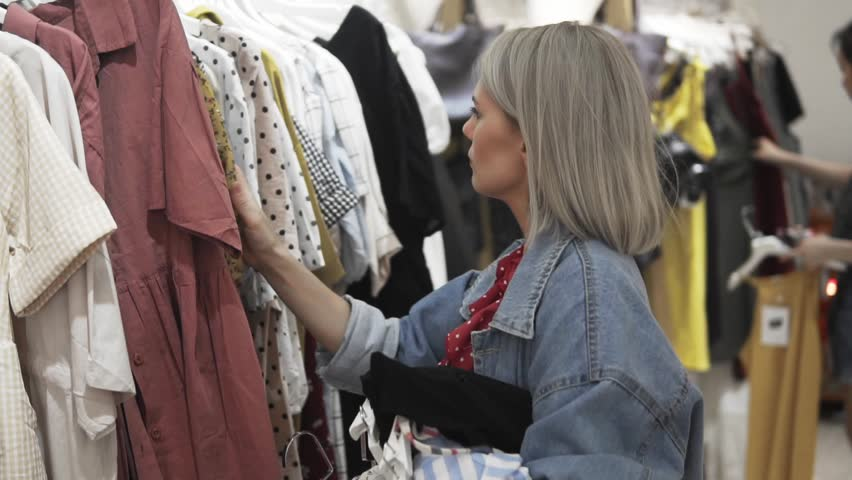 Shopping girl. Portrait of a beautiful woman in the clothes store. Young blonde girl with red lips in a clothing store. She chose a dress for a fitting. Fashionable female in stylish clothes. Fashion | Shutterstock HD Video #1013554583