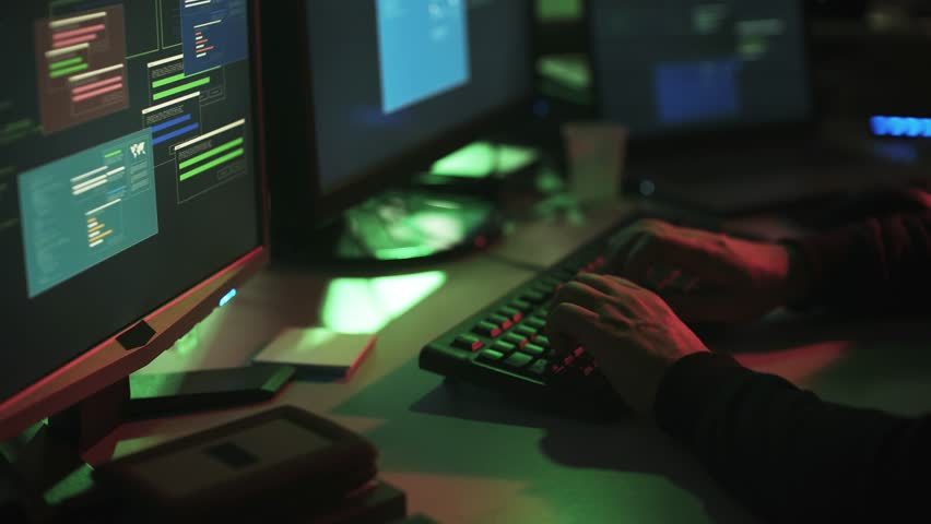 Nerd hacker with hoodie working at desk late at night, he is watching multiple screens and hacking networks, cyber security concept | Shutterstock HD Video #1013574443