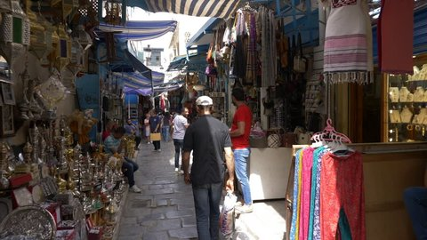 Tunis, Tunisia - 06 June 2018: traditional arabian market on narrow street in old Medina city. Tourist people walking on local bazaar and shopping arabian souvenirs and gifts.
