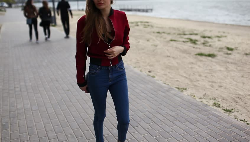 A beautiful and sexy young girl model in stylish clothes walking along the street | Shutterstock HD Video #1013593583