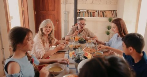 Three-generation multi-ethnic family with grandparents sitting around table and eating healthy lunch at village cottage