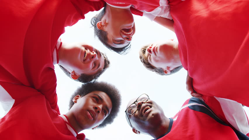 Low Angle View Of Male High School Soccer Team And Coach Having Team Talk