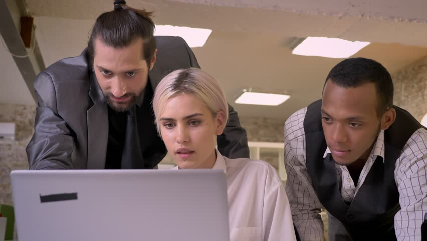 Three multy-ethnic workers discuss idea on laptop, coworking concept, communication concept, business concept | Shutterstock HD Video #1013617103