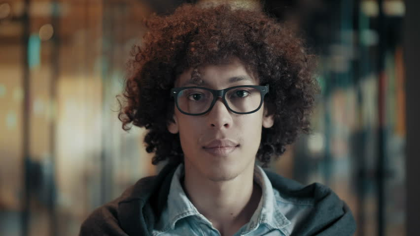 Portrait of happy smiling african young male in glasses close up face of cheerful black guy with fluffy curly black hair cute creative afro man in modern start up office looks and smiles positive mood | Shutterstock HD Video #1013618243
