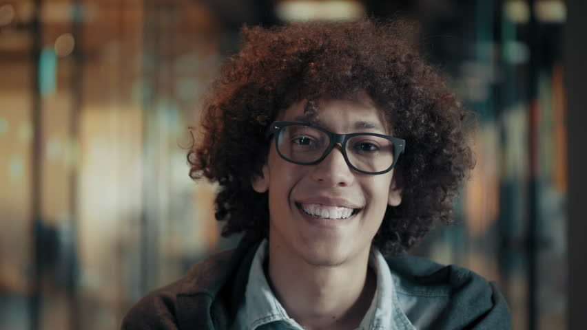 Portrait of happy smiling african young male in glasses close up face of cheerful black guy with fluffy curly black hair cute creative afro man in modern start up office looks and smiles positive mood