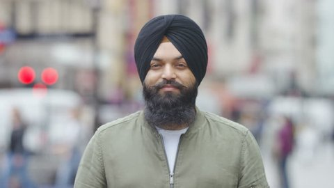 Portrait of a Sikh Indian in a turban looking to camera, in slow motion
