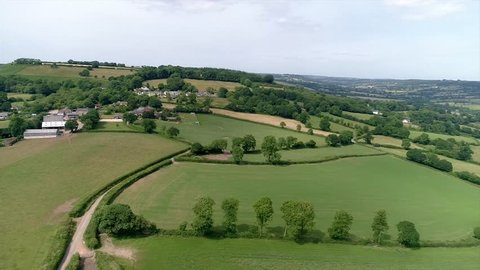 Aerial tracking forward over english fields and countryside - East Devon