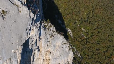 Man base jumping in slow motion from a cliff in choranche vercors massif France. Drone shot.
