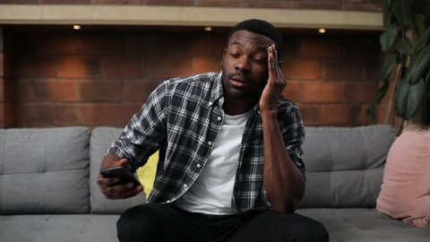 Portrait of cute guy wearing casual clothes sitting on sofa, using smartphone. Young nice African man chatting with friends, touching head. Dreadful migraine.