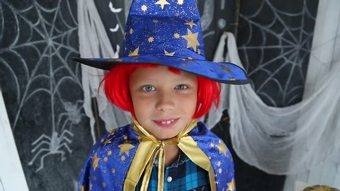 Closeup portrait of cute young boy wearing funny carnival costume and red wig ready for Halloween celebration. Funny kid screaming loudly trying to scare everyone.