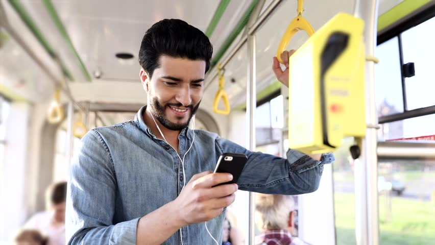 Young Bearded Man Smiling Happily While Chatting on his Smartphone. Standing in the Tram. Holding the Handrails. Sltylishly Dressed. Luxurious Watch on his Wrist. Neat Hairstyle.